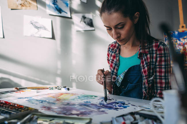 Female artist painting at table in art studio — Stock Photo