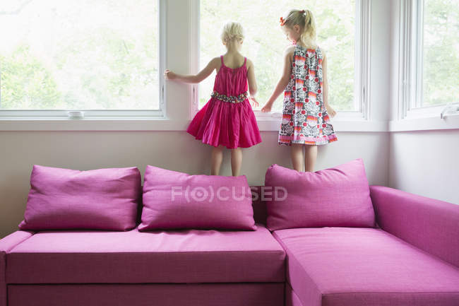 Sisters standing on pink sofa by window at home — Stock Photo