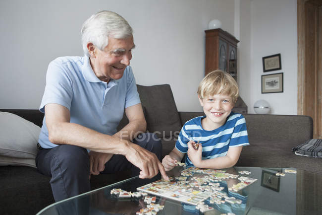 Happy grandson and grandfather sitting with jigsaw puzzle in living room — Fotografia de Stock