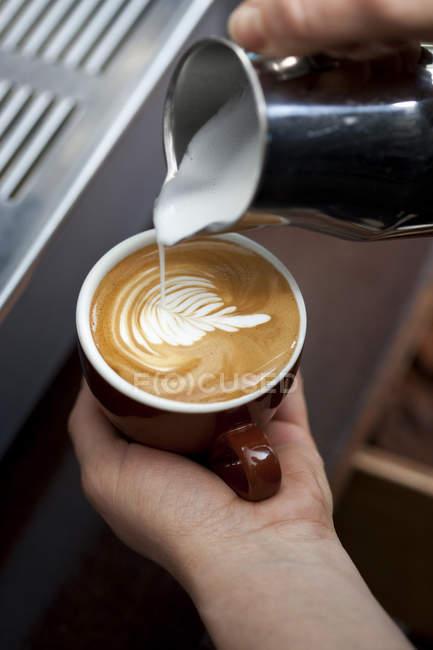 Обтинання barista руки прикраси молоко піна з квітковим візерунком — стокове фото