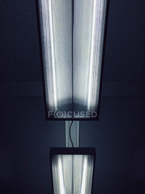 Low angle view of illuminated fluorescent lights on ceiling — Stock Photo