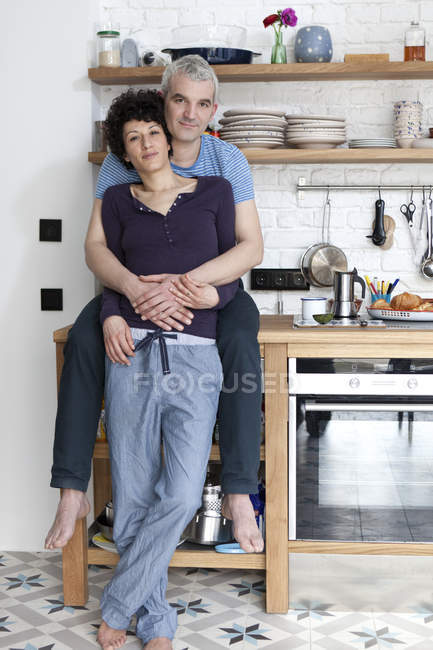Portrait of affectionate smiling mixed age couple embracing in kitchen — Stock Photo