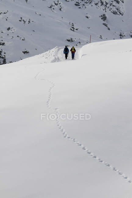 Rear view of two people in distance walking on snow hike — Stock Photo