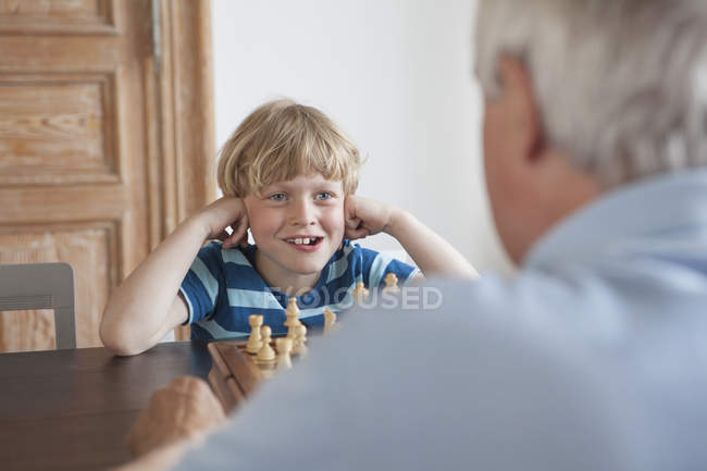 Happy little boy playing chess with grandfather at home — Stock Photo
