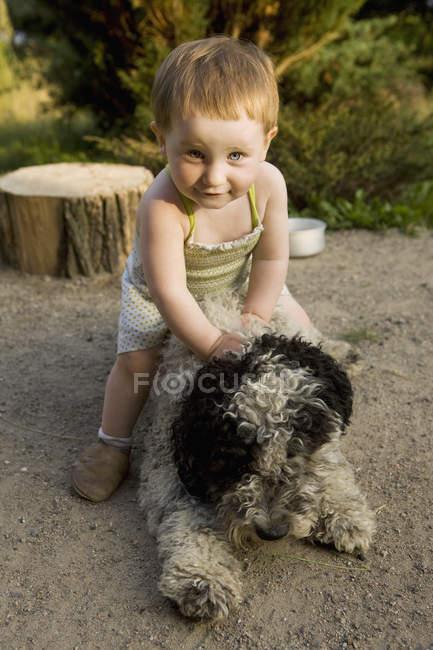 Mädchen spielt mit portugiesischem Wasserhund auf dem Land — Stockfoto
