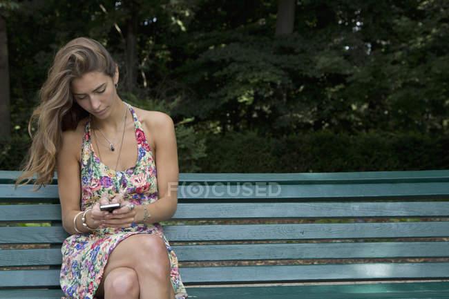 Молода жінка, сидячи на лавці парку, за допомогою мобільного телефону — стокове фото