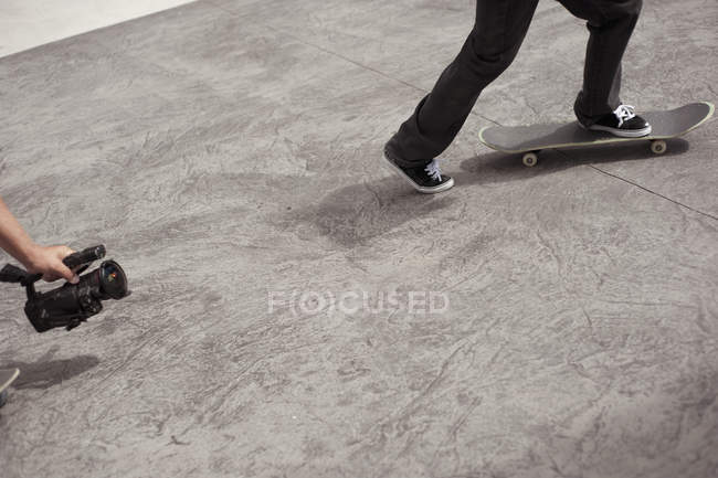 Cropped image of man video shooting friend skateboarding in park — Stock Photo