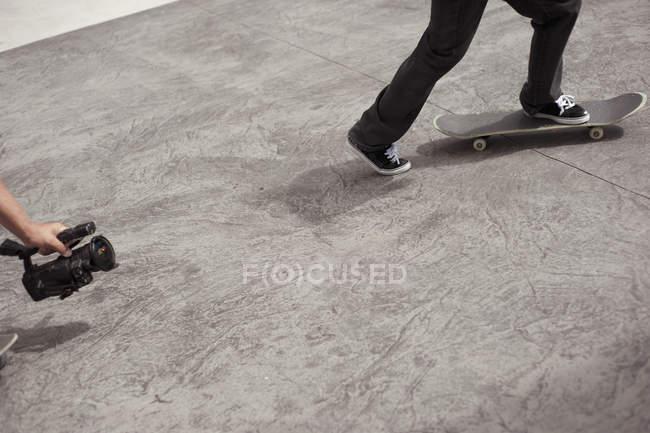 Cortada a imagem de vídeo de homem tiro amigo andando de skate no parque — Fotografia de Stock