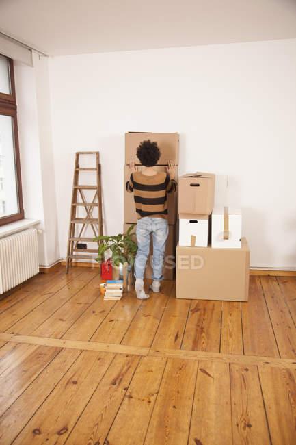 Visão traseira da mulher empurrando caixa em movimento em cima da pilha no quarto — Fotografia de Stock