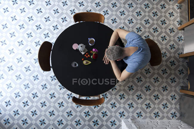 From above view of man sitting at table with head resting on arms — Stock Photo