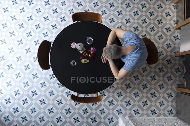 Сверху вид человека, сидящего за столом с головой, опираясь на руки — стоковое фото