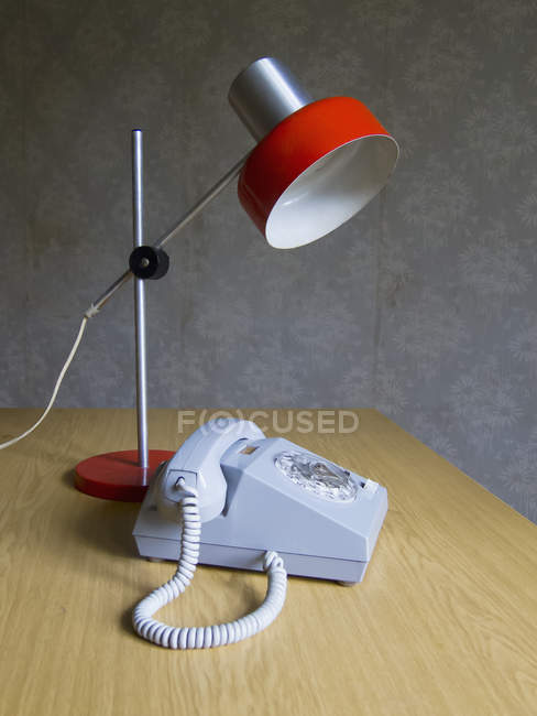 Rotary phone and electric lamp on table at home — Stock Photo