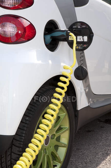 Close up view of charger connected to electric car recharging — Stock Photo