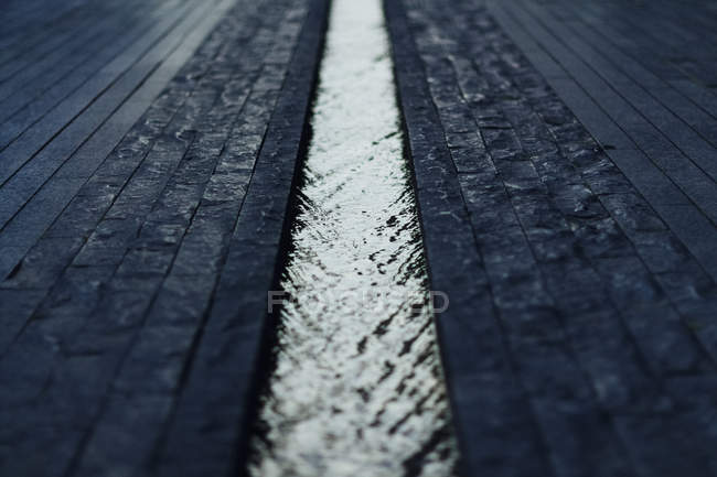 Close up view of narrow gutter stream on sidewalk — Stock Photo