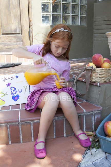 Menina vendendo maçãs no alpendre e derramar suco de jarro — Fotografia de Stock