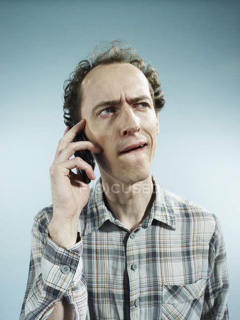 Man using mobile phone with confused look on face — Stock Photo