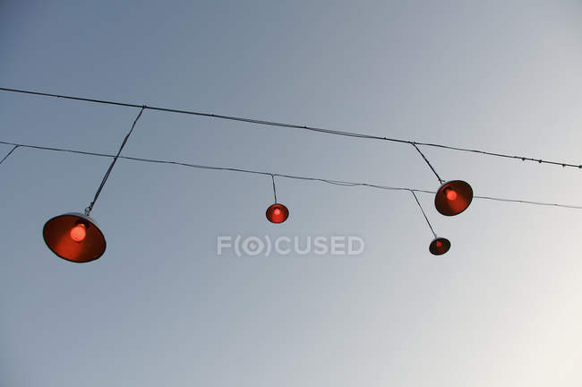Cabos com lâmpadas penduradas sobre o céu azul — Fotografia de Stock