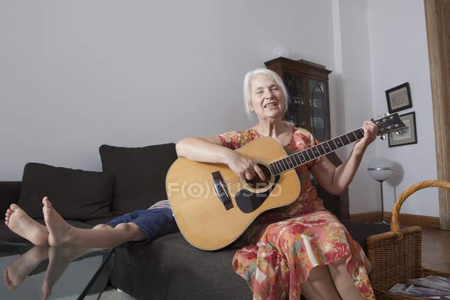 Старшие женщины пели песни и играл на гитаре на дому с внуком на фоне — стоковое фото