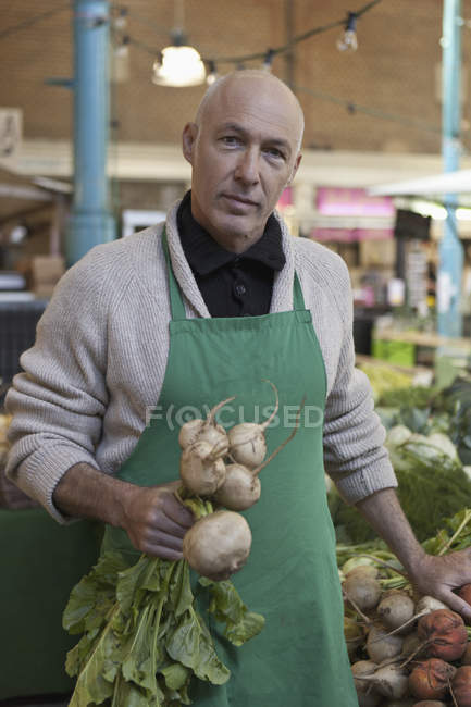 Portrait of salesman holding turnips at farmer market — Stock Photo