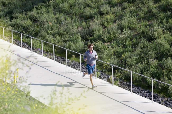 Mitte erwachsener Mann joggt auf Fußweg im Park — Stockfoto