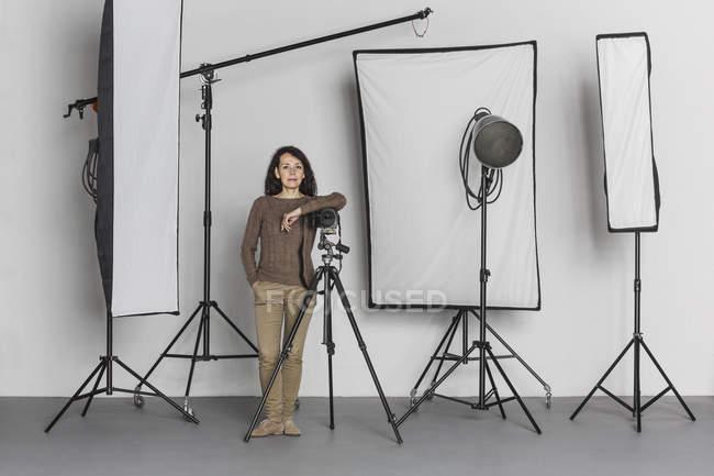Full length of confident mature female photographer in photo studio — Stock Photo