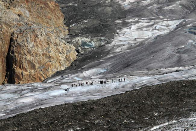 Vista de los excursionistas a pie en terreno montañoso - foto de stock