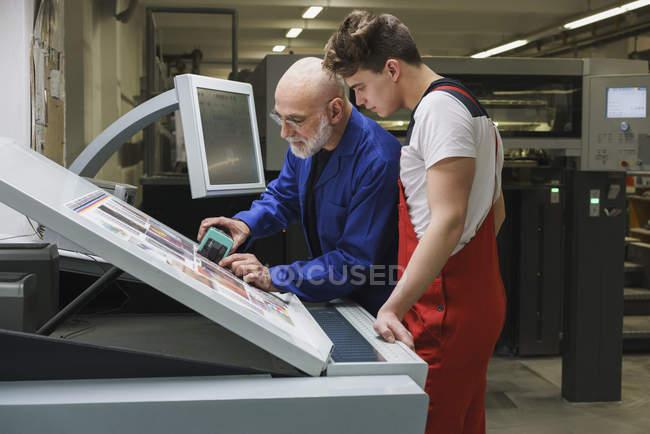 Trabalhador maduro mostrando colega qualidade de impressão com scanner na imprensa — Fotografia de Stock