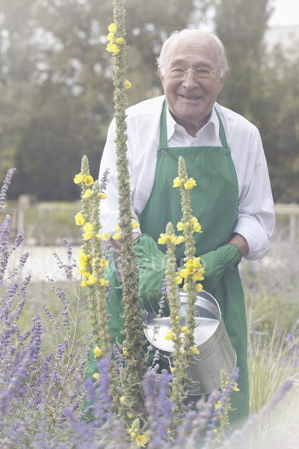 Portrait of Senior man watering plant in garden — Stock Photo
