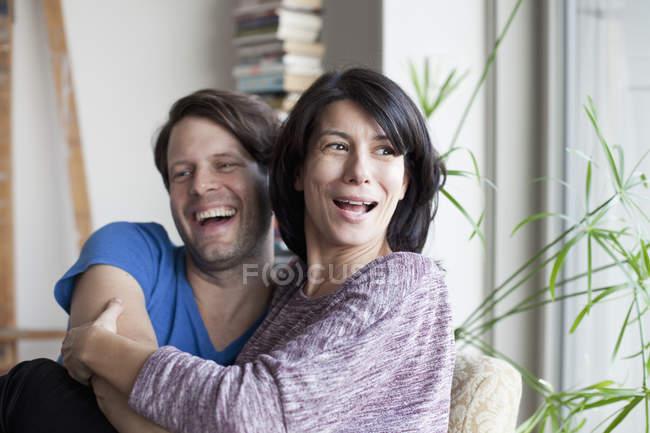 Pareja abrazándose uno al otro y sonriendo en el hogar - foto de stock