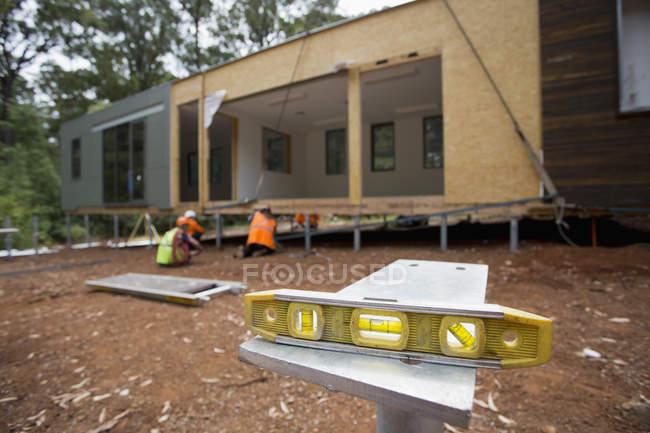 Уровень на таблице на фоне строительной площадки — стоковое фото