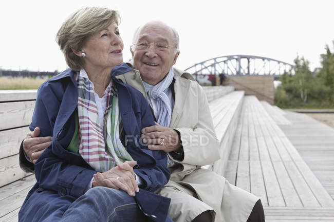 Laughing senior couple sitting on wooden steps in park — Stock Photo