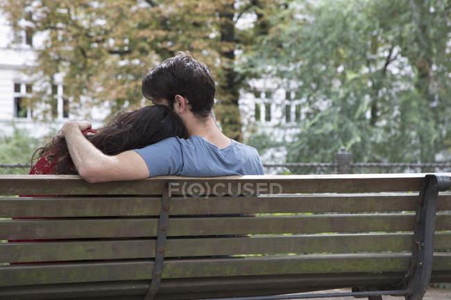 Вид сзади Молодая пара сидит на скамейке в парке — стоковое фото