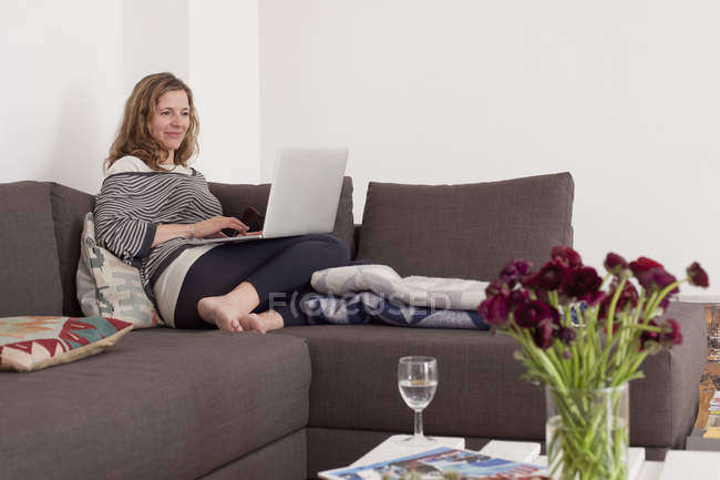 Woman using laptop on sofa in living room — Stock Photo