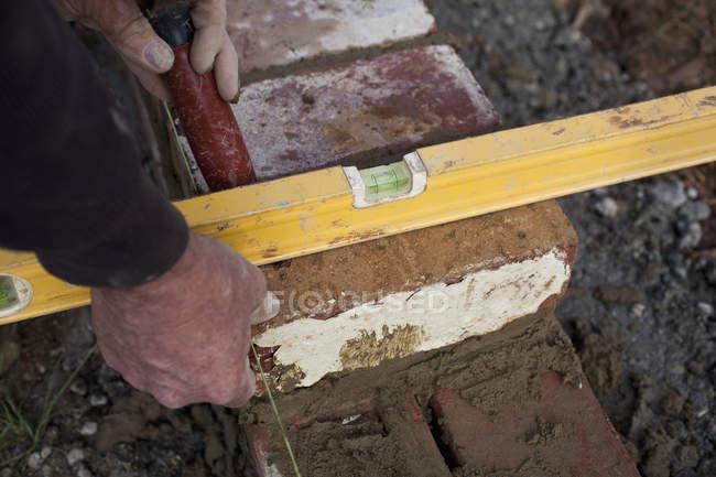 Урожай мужской руки проверка кирпича стены уровни — стоковое фото