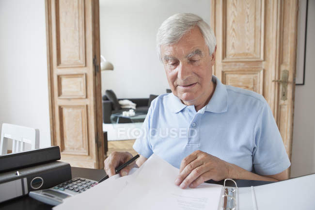 Senior man reviewing financial documents at table — Stock Photo