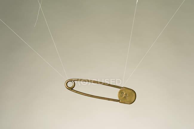 Stringhe legate al perno di sicurezza appeso sullo sfondo bianco — Foto stock