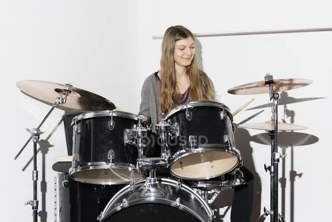 Молода жінка, посміхаючись хоча грати на барабанах — стокове фото