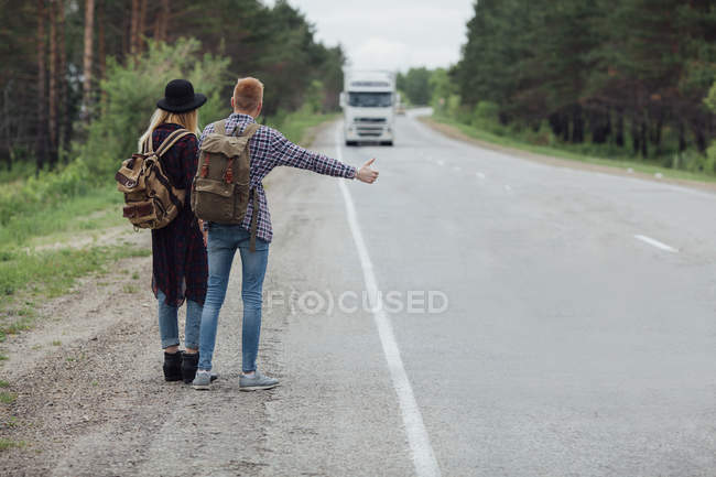 Rear view of young couple hitchhiking on roadside — Stock Photo