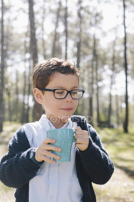 Хлопчик тримає кухоль кави в лісі — стокове фото
