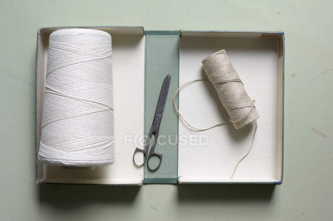 Directly above view of thread spools and scissors in box on table — Stock Photo