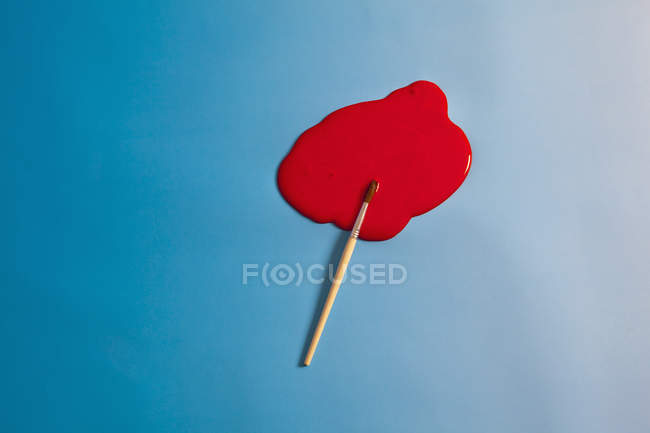 Paintbrush and puddle of red paint on blue background — Stock Photo