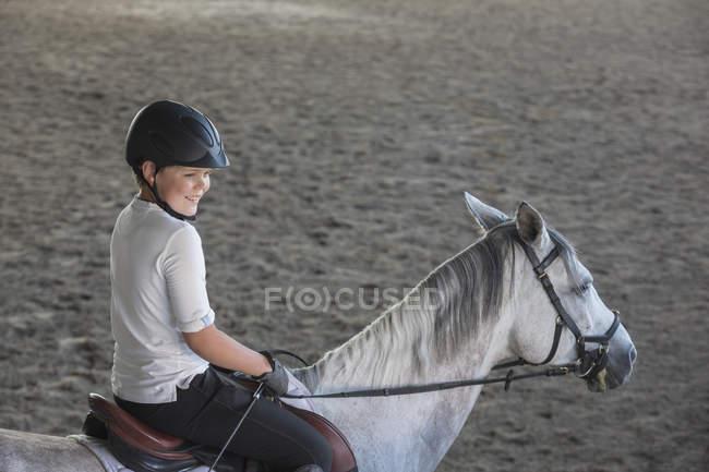 Vista lateral do menino sentado a cavalo no estábulo de treinamento — Fotografia de Stock