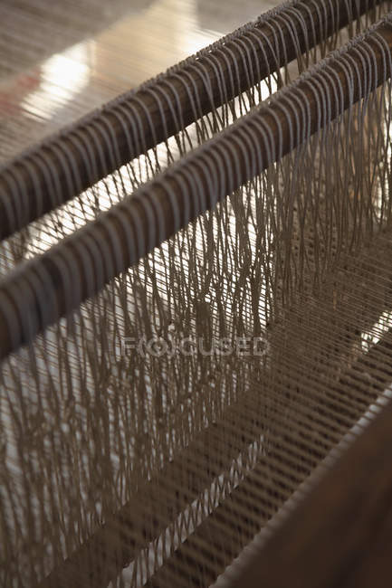 Close up view of threads in loom machine with — Stock Photo