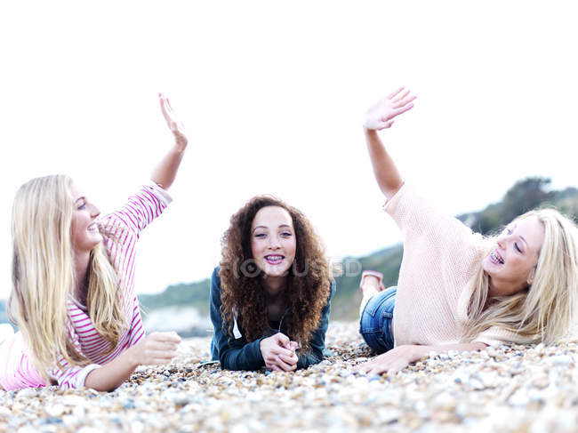 A girl lying in between two friends high-fiving above her at the beach — Stock Photo