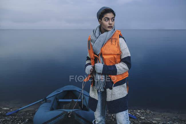 Девочка-подросток, надувной плот на берегу озера зимой — стоковое фото