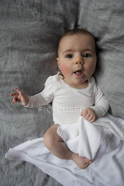 Retrato de menina bonito, deitada na cama — Fotografia de Stock