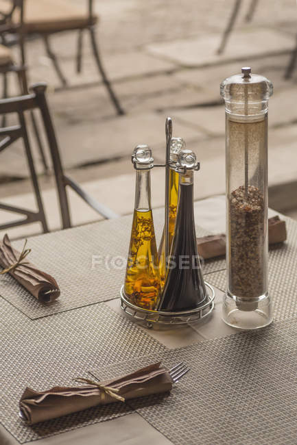 Close up view of seasoning bottles and napkins on table in restaurant — Stock Photo