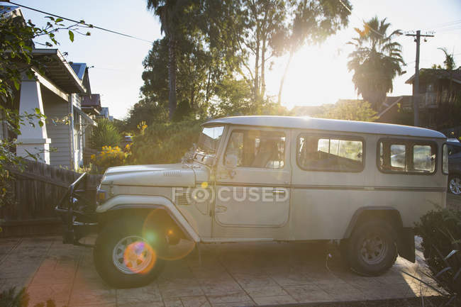 Sports utility vehicle parked at house yard by trees on sunny day — Stock Photo