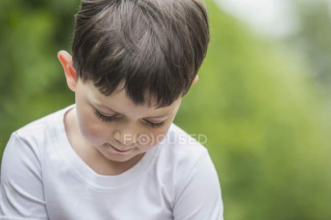 Симпатичный мальчик, смотрящий в парк — стоковое фото