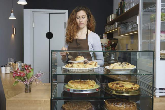 Вид спереду, жінки, яка виступає кориці рулонах стоячи в кафе — стокове фото